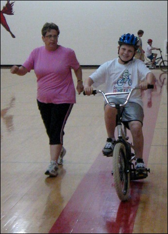 Dawn Tierney walks alongside her son, Michael Tierney, as he learns to ride a bicycle in the Lose the Training Wheels camp held at Union Grove Elementary School this week.